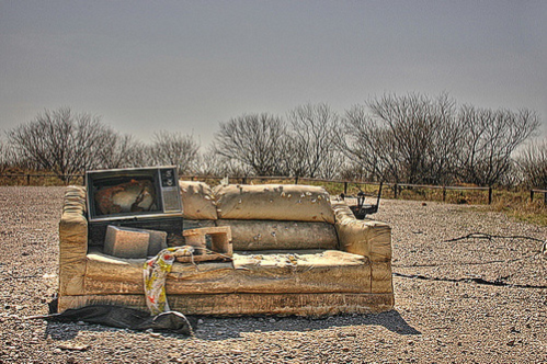 A photo of an old couch with a microwave and other trash placed on top of it.