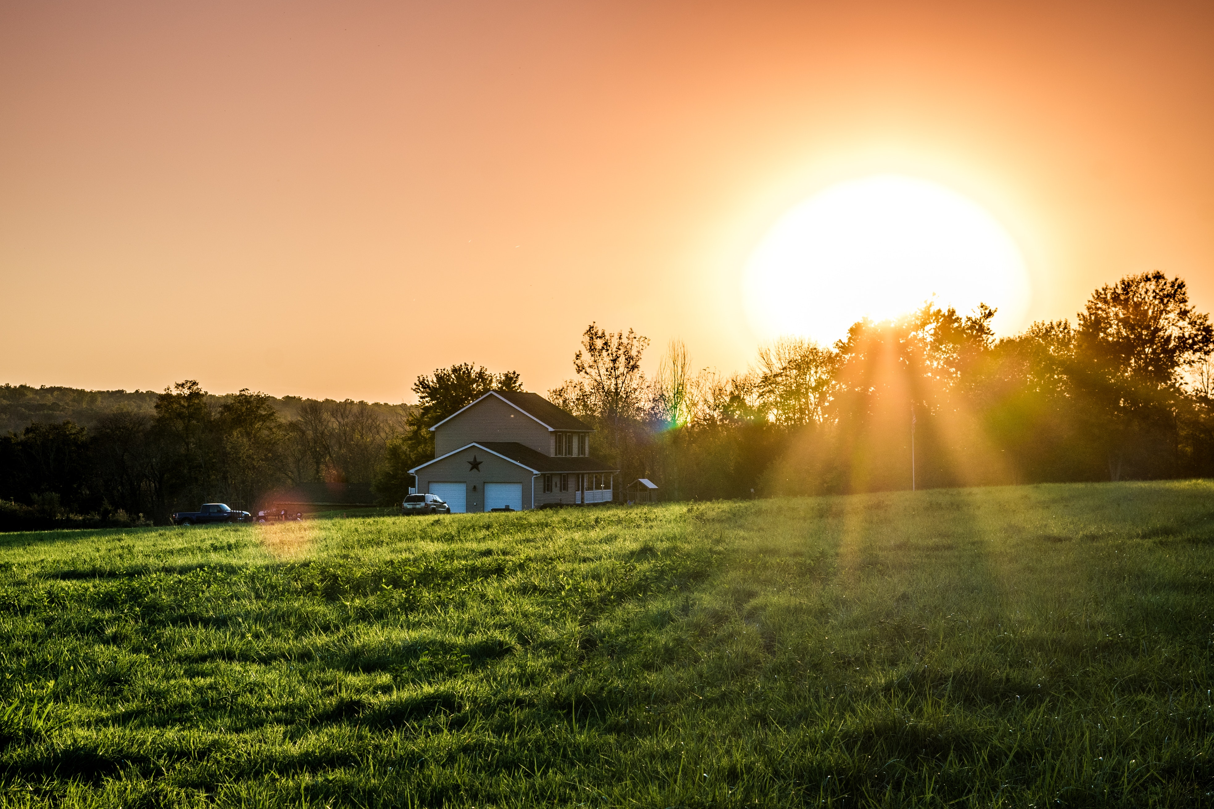 A photo of a house with the sun rising behind it.